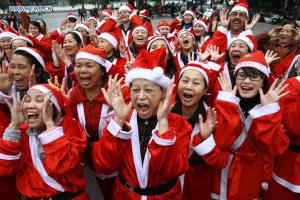 """Members of the ""Laughter Yoga"" club participate in an event called ""Christmas Smile"" near the Hoan Kiem Lake in Hanoi, Vietnam, on Dec. 23, 2012. (Xinhua/Ho Nhu Y)"